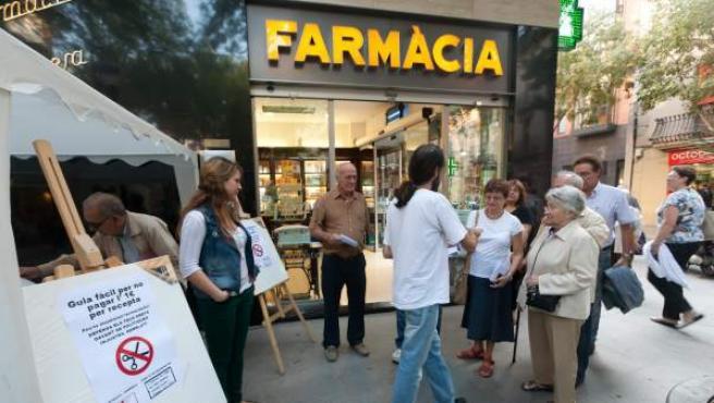 Una manifestante muestra, dentro de una farmacia, una guía rápida sobre cómo no pagar la tasa.