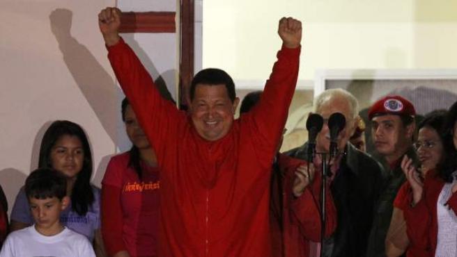 El presidente de Venezuela, Hugo Chávez saluda desde un balcón del palacio de Miraflores, en Caracas (Venezuela) después de ganar las elecciones.