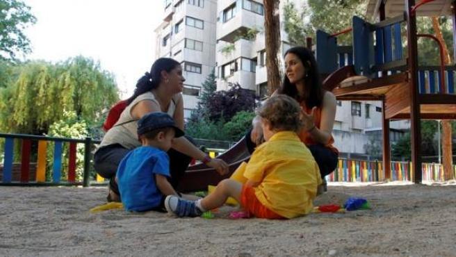 Dos madres con sus hijos en una zona infantil en el barrio del Pilar.
