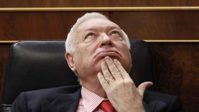 El ministro de Asuntos Exteriores y de Cooperación, José Manuel García-Margallo, escucha desde su escaño las intervenciones del debate de convalidación del Decreto Ley de Medidas urgentes en materia presupuestaria en una pose curiosa.