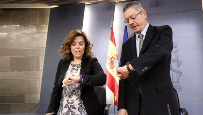 La vicepresidenta del Gobierno, Soraya Sáenz de Santamaría, y el ministro de Justicia, Alberto Ruíz-Gallardón, miran el reloj poco antes de la rueda de prensa del Consejo de Ministros.