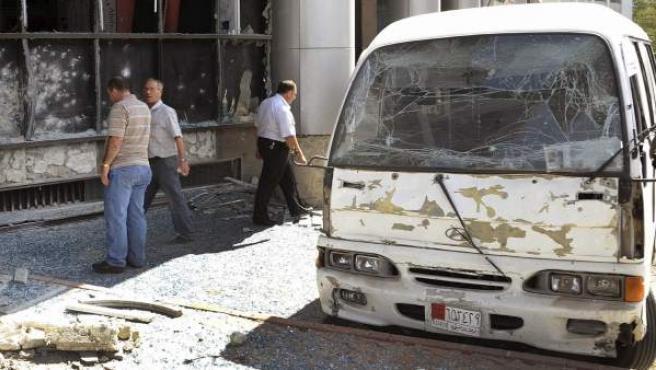 Ciudadanos sirios pasando por el lugar donde se registró la explosión de una bomba al paso de un vehículo en el barrio de al-Zablatani en Damasco.