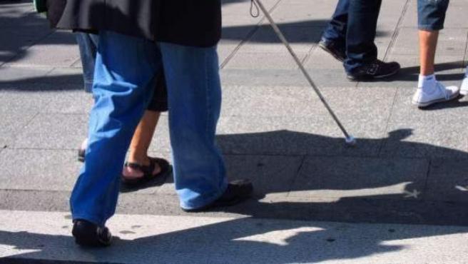 Una persona invidente caminando por la calle.