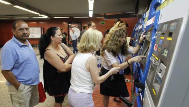 Una supervisora de Metro ayuda a los viajeros a sacar un billete
