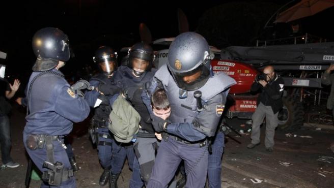 Varios policías reducen a un manifestante en la plaza de Neptuno.