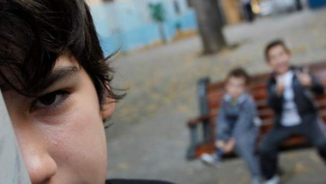 Emilio, que ha vivido tres desahucios, y sus hermanos pequeños, en una plaza pública de Vallecas, Madrid.
