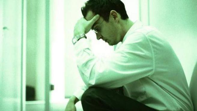 Un hombre estresado en su puesto de trabajo.