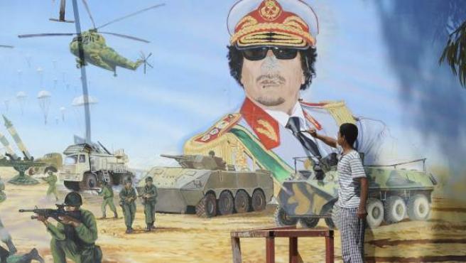 Un joven utiliza un objeto punzante para destruir una pintura mural que representa al líder libio, Muamar el Gadafi.