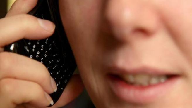 Una mujer habla por su teléfono móvil.