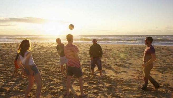 Un grupo de adolescentes juegan al voleibol en la playa.
