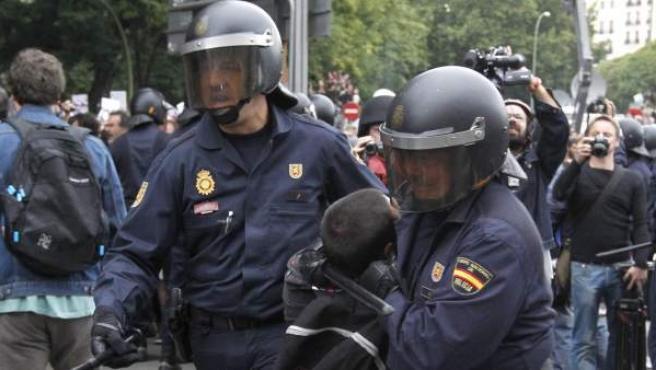 Dos policías conducen a uno de los detenidos en la protesta del 25-S en la plaza de Neptuno.