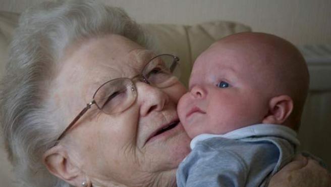 Una abuela levanta en brazos a su nieto.