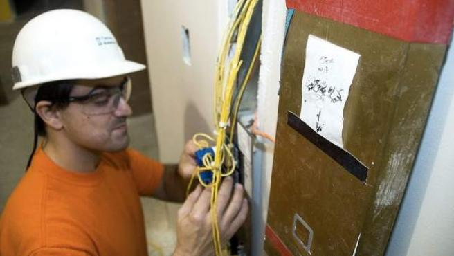 Un electricista revisando los cables de una instalación.