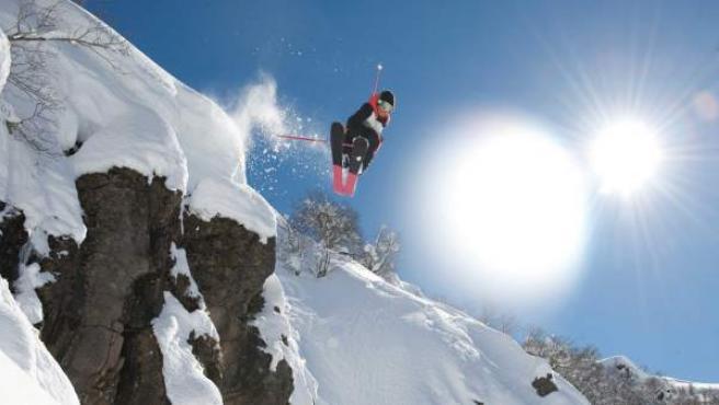 Un esquiador realiza un salto en una ladera nevada.