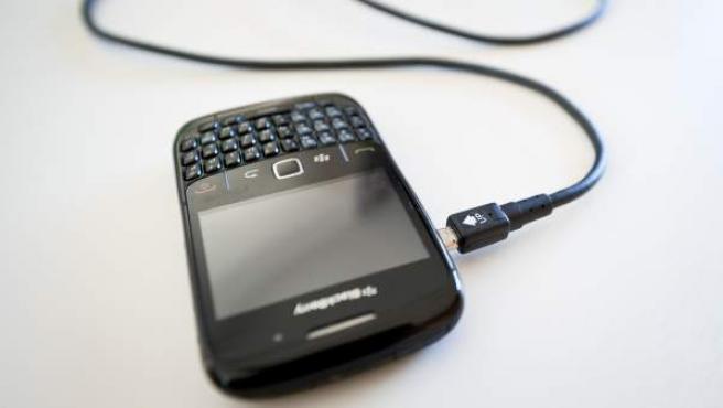 Un cable cargador de móvil, con una blackberry.