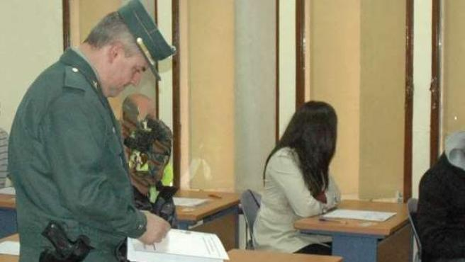 Un agente de la Guardia Civil revisando el DNI de un hombre, durante un examen teórico de conducir.