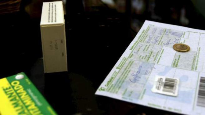Una persona adquiere un medicamento en una farmacia catalana abonando la tasa de un euro por receta.