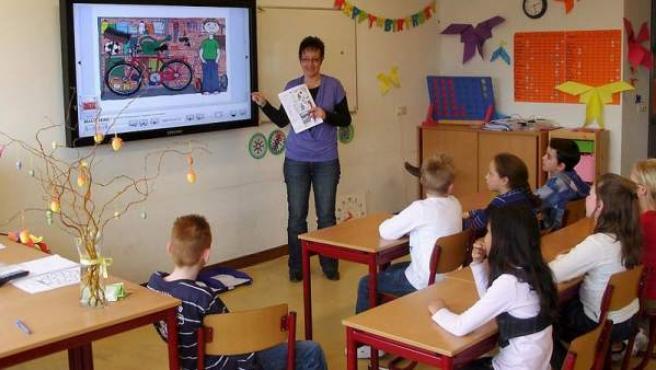 Una profesora imparte clases de inglés a sus alumnos de primaria.