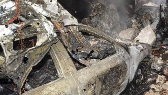 Imagen cedida por la Agencia de Noticias SANA que muestra los escombros de un coche bomba detonado en Damasco, Siria.