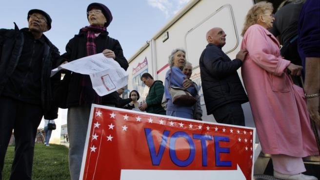Tj Cheng y su mujer Quin Wang, de East Windsor (Nueva Jersey, EE UU), hacen cola para votar a las puertas de un centro de votación móvil en Burlington, Nueva Jersey. El presidente Barack Obama se enfrenta al republicano Mitt Romney en las elecciones que decidirán quién dirigirá el país norteamericano durante los próximos cuatro años