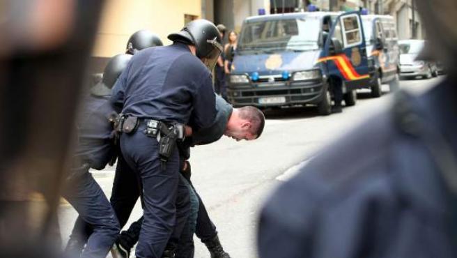 La Policía Nacional se lleva a un hombre detenido en un desahucio en Oviedo.