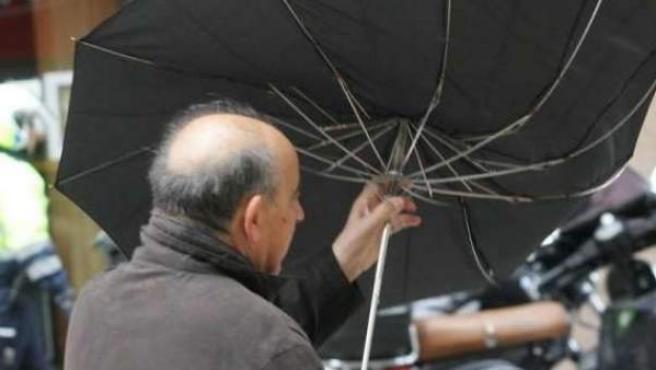 Un hombre sujeta su paraguas contra el fuerte viento en una imagen de archivo.