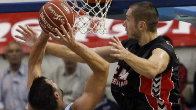 El pívot del UCAM Murcia Kim Tillie (d) intenta bloquear al también pivot del Real Madrid Felipe Reyes (c), durante el partido correspondiente a la sexta jornada de la fase regular de la liga ACB disputado entre ambos equipos en el Palacio de los Deportes de Murcia.