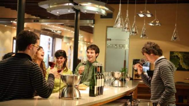Un grupo de jóvenes disfrutando de unas copas de vino.