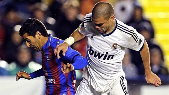 """El delantero del Levante Ángel Rodríguez (i) controla la pelota presionado por el defensa portugués del Real Madrid Képler Lima """"Pepe""""."""