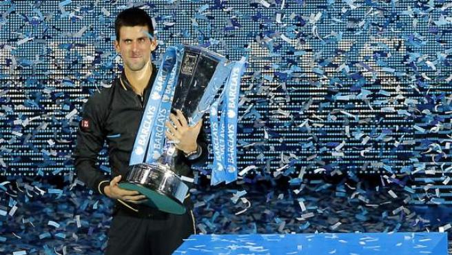 El tenista serbio Novak Djokovic posa con el trofeo de la Copa de Maestros tras vencer al suizo Roger Federer hoy.