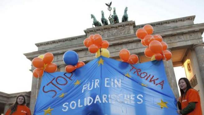 Unos manifestantes, frente a la Puerta de Brandenburgo en Berlín, Alemania, portan con una bandera en la que se lee 'Por el Trabajo y la Solidaridad', el pasado miércoles.