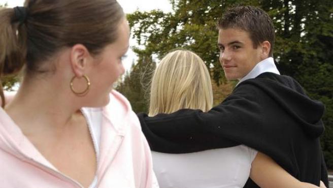 Un adolescente mira a otra chica mientras pasea con su novia.