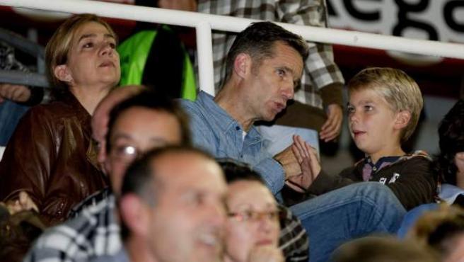 Iñaki Urdangarin, la infanta Cristina y uno de sus hijos en la grada del Palau durante un partido del Barça de balonmano.