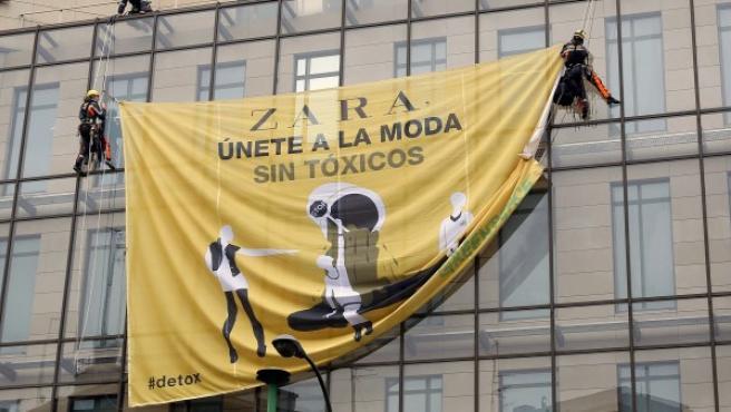 Activistas de Greenpeace se descuelgan de la fachada de Zara en la calle Princesa de Madrid.