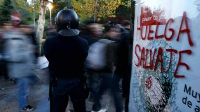 Un agente de Policía vigila en la Ciudad Universitaria de Madrid junto a una pintada relativa a la jornada de huelga general del 14-N.