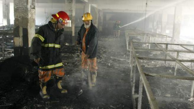 Varios bomberos refrescan una de las plantas del edificio donde se ha producido el incendio.