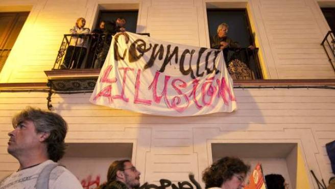 Varias personas cuelgan una pancarta en los balcones del edificio que dieciocho familias han ocupado en Sevilla.