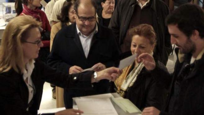 Varias personas hacen cola para ejercer su derecho al voto en las elecciones autonómicas en un colegio de Barcelona. La participación este 25-N ha sido del 29,35% a las 13.00 horas, 4,5 puntos más que en los comicios al Parlament del 28 de noviembre de 2010.