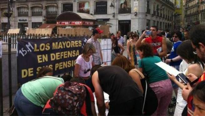 Un grupo de personas simpatizantes del 15-M recogen firmas en la Puerta del Sol contra la congelación de las pensiones y presentar así una ILP en el Congreso.