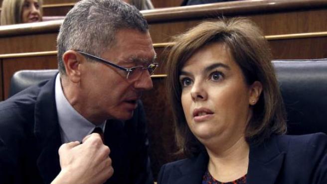 El ministro de Justicia, Alberto Ruiz Gallardón, conversa con la vicepresidenta del Gobierno, Soraya Sáenz de Santamaría, durante la sesión de control al Gobierno.