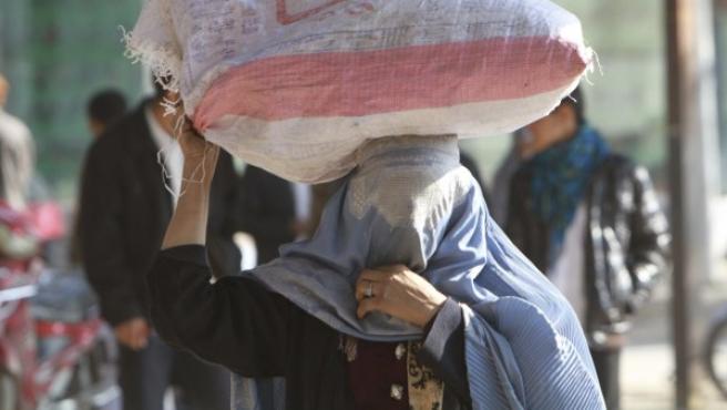 Una mujer vestida con burka carga con un saco por las calles de Afganistán.