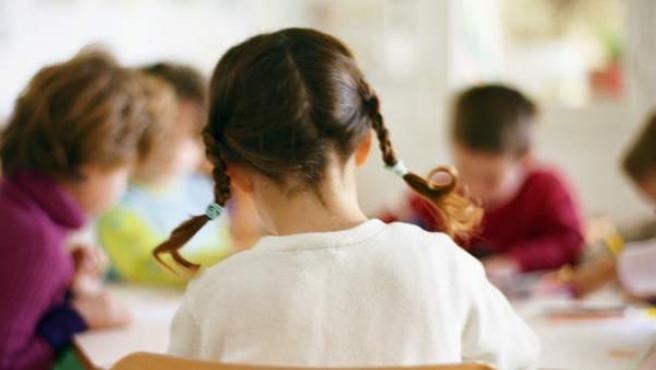 Una niña, estudiando en clase.