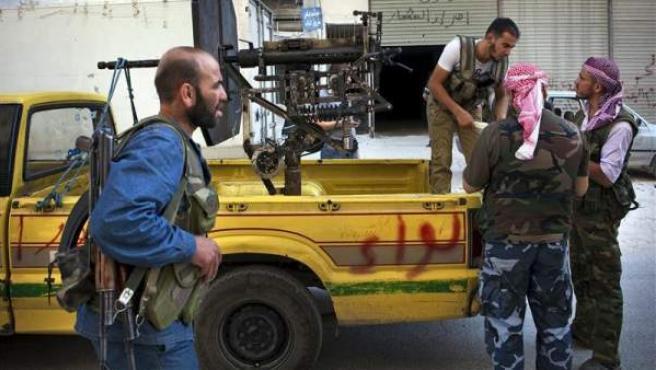 Soldados del rebelde Ejército Libre Sirio (ELS) cargan arsenal antiaéreo en una furgoneta aparcada en una calle del barrio de Shaa, en la ciudad siria de Alepo.