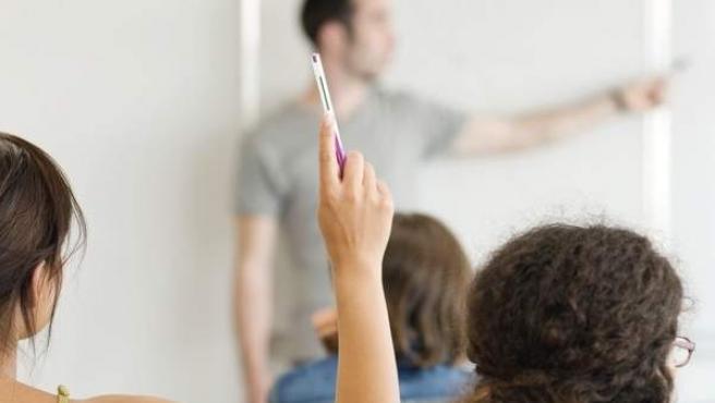 Una alumna levanta la mano en clase durante una explicación del profesor.