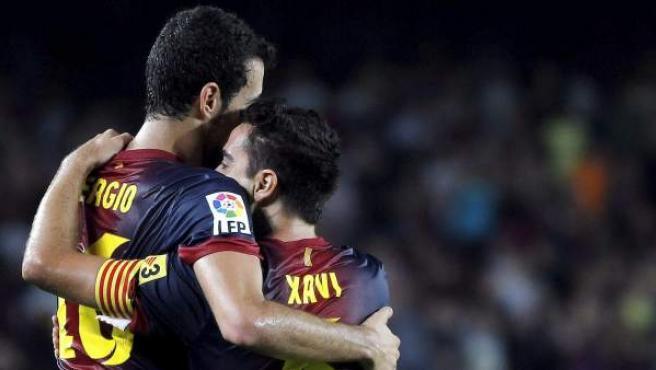 Busquets y Xavi se abrazan durante una celebración.