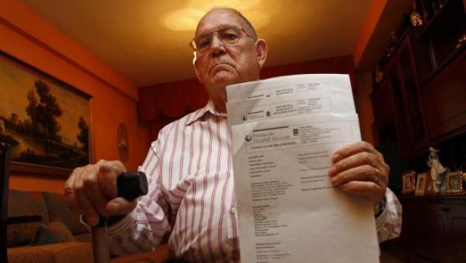Gregorio Gaitán, en su casa, mostrando los informes de su operación de cataratas.