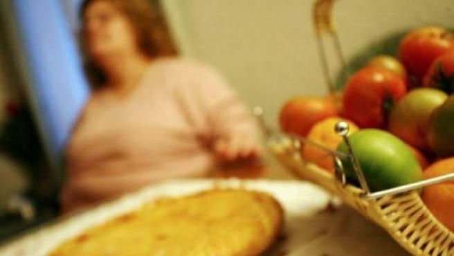 Una mujer obesa ante una mesa con varios alimentos.