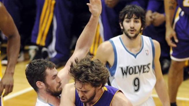 El jugador de los Lakers Pau Gasol (d) disputa el balón con Kevin Love (i) de los Timberwolves, junto al español Ricky Rubio (atrás).