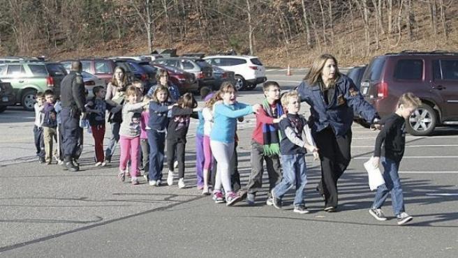 Fotografía cedida que muestra a unos agentes de Policía evacuando a unos niños de la escuela Sandy Hook en Newtown (Connecticut, EE UU).