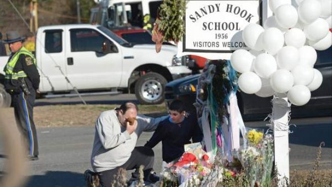 Un hombre y su hijo se acercan este sábado a las inmediaciones de la esuela infantil de Newtown donde este viernes fallecieron 20 niños y seis adultos como consecuencia de un tiroteo.